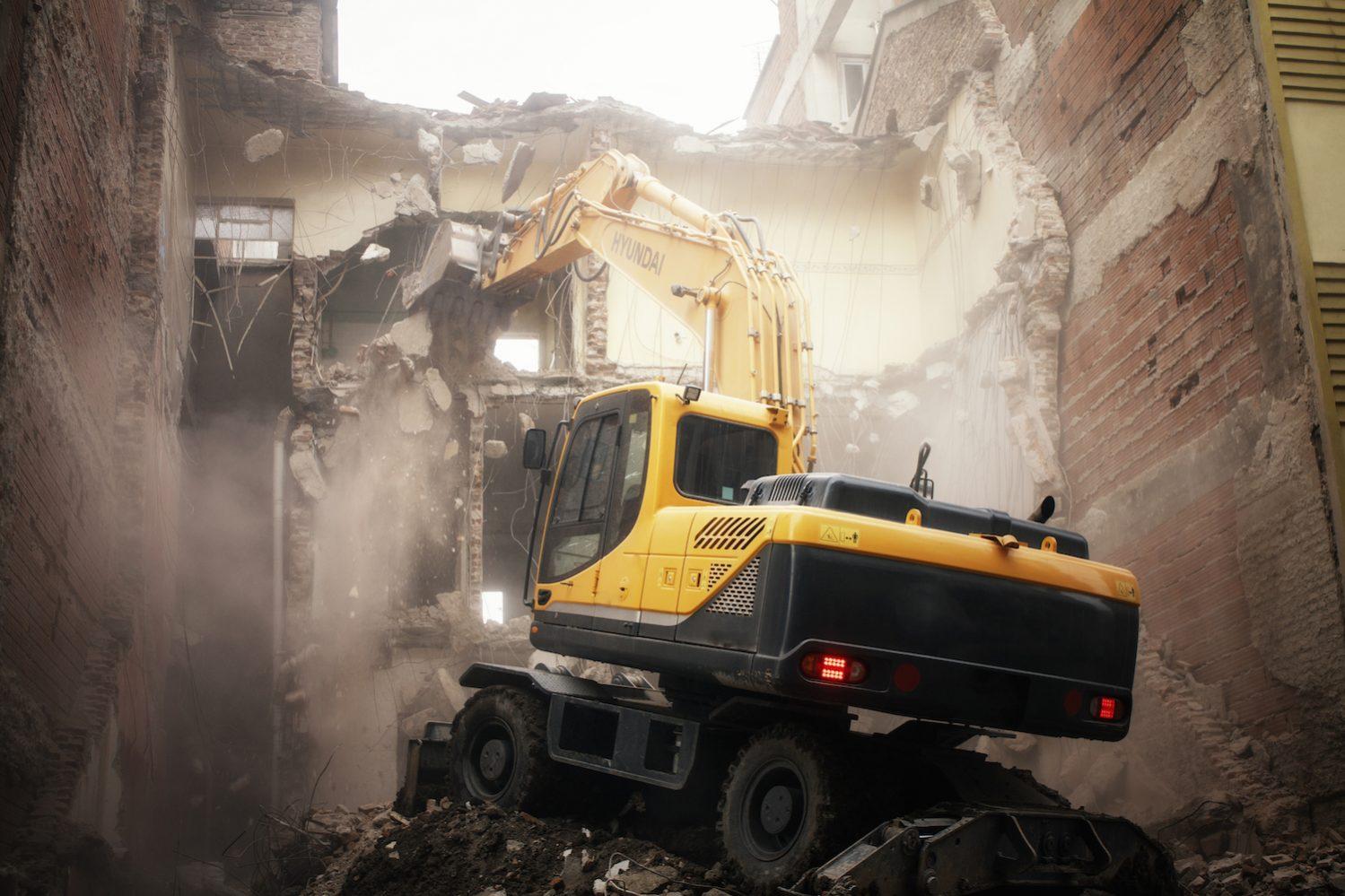 Yellow excavator demolishing abandoned brick building