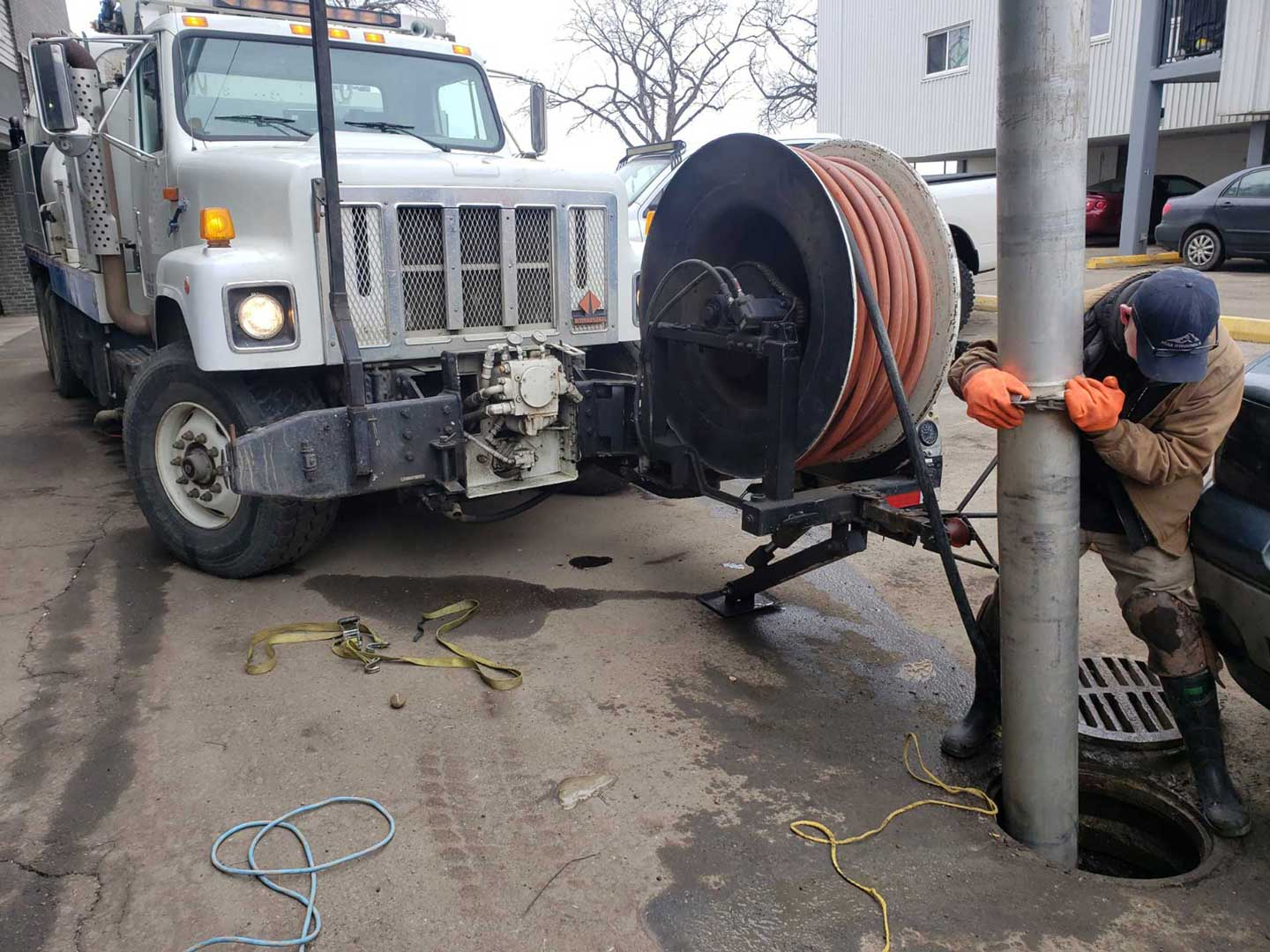 Hydrovac truck with worker cleaning manhole
