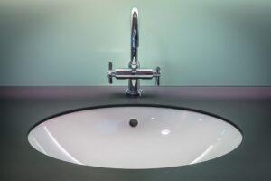 Modern chrome bathroom sink against teal wall