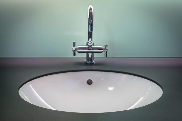 Modern chrome bathroom sink against teal wall