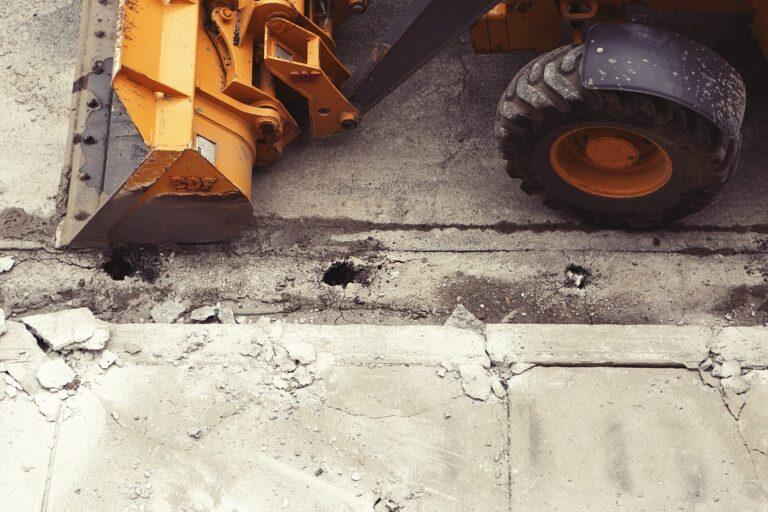 Yellow excavator next to cracked sidewalk