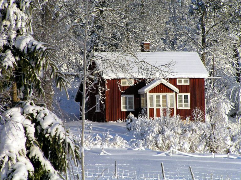 Red brick home with snow-covered roof in front of a forest in winter