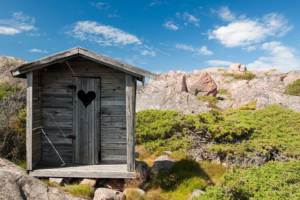 Wooden outhouse in front of shrubs and rocks