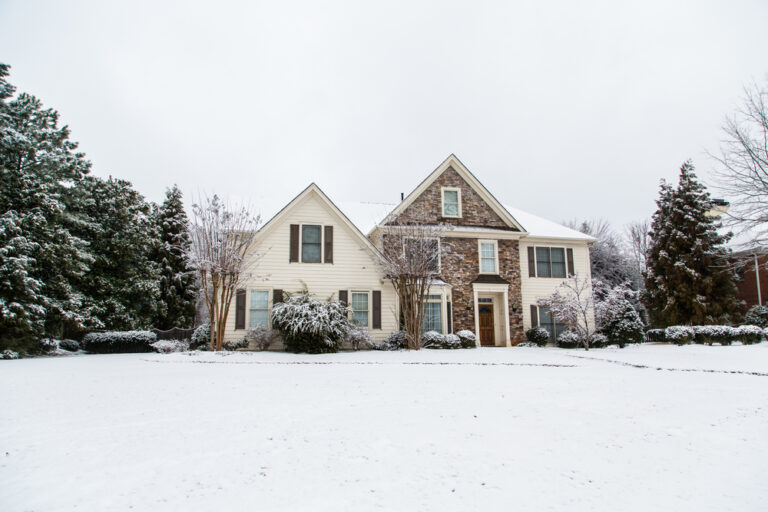 large white and brown brick home with snowy front lawn