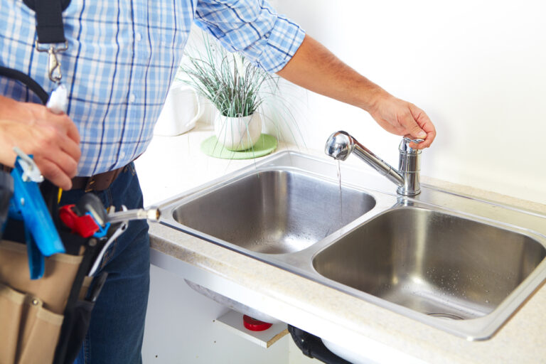 plumber with blue plaid shirt and tool belt using sink after repair