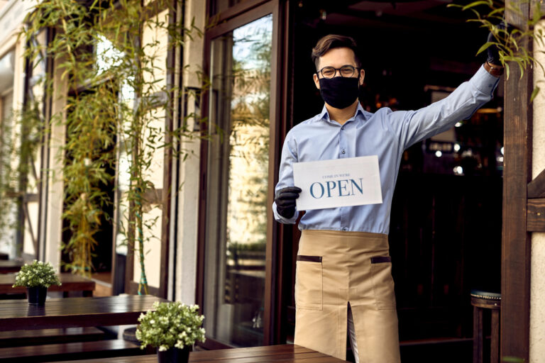 male server with glasses and brown apron and black face mask holding an open for business sign. he is standing on the patio of a cafe with brown chairs and tables.