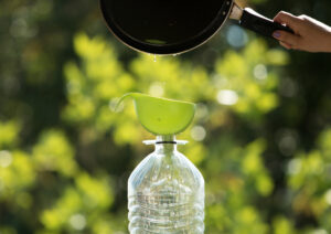 skillet pouring grease into a green funnel placed over plastic water bottle
