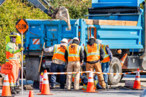 group of construction workers in orange vests stand in front of blue dump truck